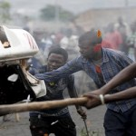 Protesters destroy a car belonging to a policeman after they intercepted him at a barricade during demonstrations in Bujumbura